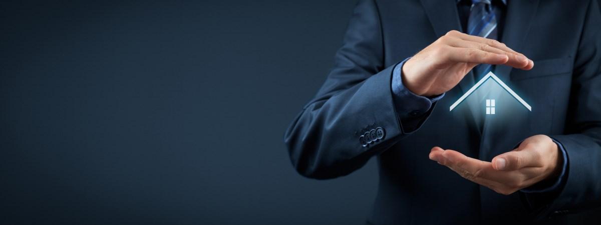 Zwei schützende Hände eines Anwalts über einem Haus. Eine symbolische Darstellung des Themas Asset Protection, auf deutsch Vermögensschutz.