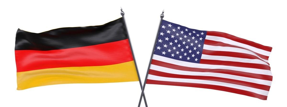 Eine amerikanische Flagge und eine deutsche Flagge. Die Fahnenhalterungen kreuzen sich.