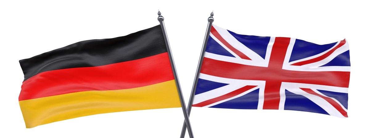 Eine britische Flagge und eine deutsche Flagge. Die Fahnenhalterungen kreuzen sich.