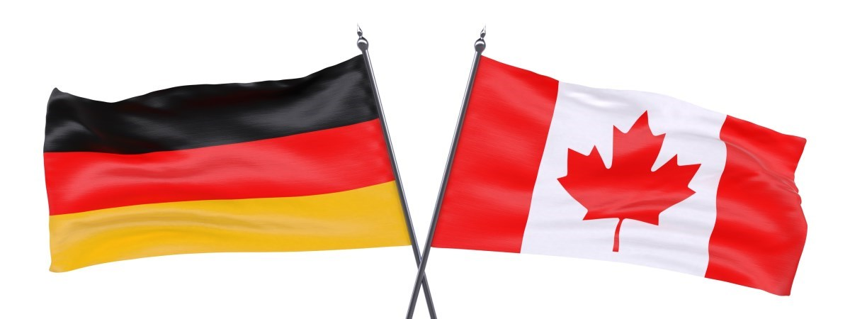 Eine kanadische Flagge und eine deutsche Flagge. Die Fahnenhalterungen kreuzen sich.