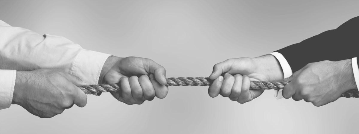 Zwei mal zwei Männerhände ziehen an einem Tau. Gesellschafterstreitigkeiten können häufig ein buchstäbliches Tauziehen werden.