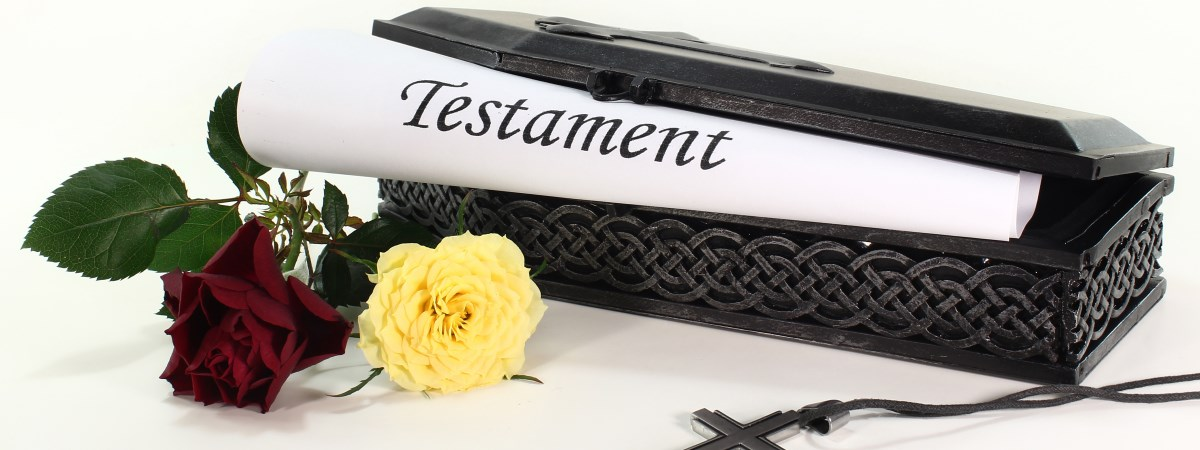 """Small coffin with a scroll, where there is """"testament"""" written on it, adorned with a red and a yellow rose and a crucifix necklace."""